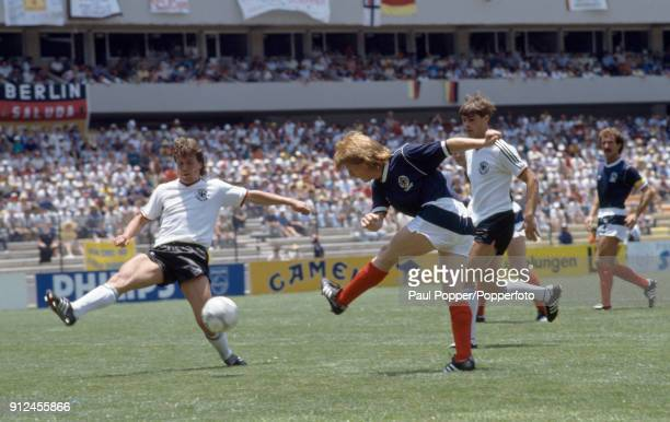 Gordon Strachan shoots past West Germany's Lothar Matthaeus to score Scotland's goal during the FIFA World Cup match between Scotland and West...