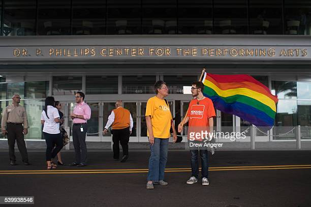Gordon Woodworth III carries a Pride flag on his way to an evening vigil for the victims of the Pulse Nightclub shootings at the Dr Phillips Center...