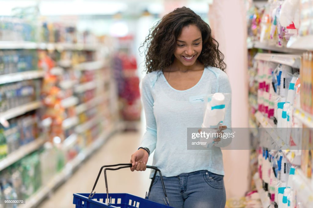 Gorgeous black woman at the supermarket buying products reading the label looking very happy : Stock Photo