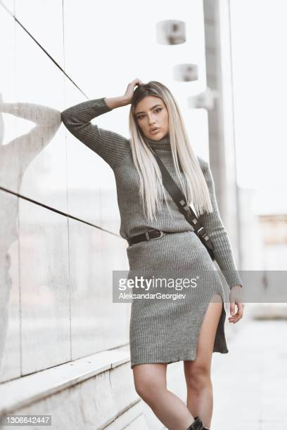 gorgeous blond female leaning on marble wall outside - bending over in skirt stock pictures, royalty-free photos & images