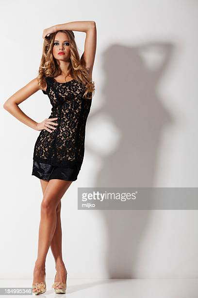 gorgeous blonde posing in mini dress - skinny black woman stock photos and pictures