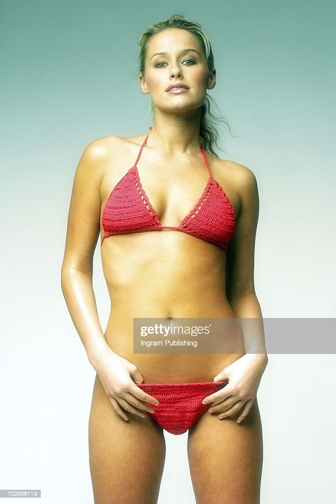 Gorgeous blonde woman poses in a red bikini in the studio. : Stock Photo
