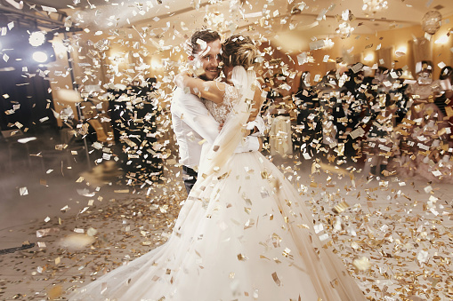 Gorgeous bride and stylish groom dancing under golden confetti at wedding reception. Happy wedding couple performing first dance in restaurant. Romantic moments 1050000538