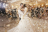 Gorgeous bride and stylish groom dancing under golden confetti at wedding reception. Happy wedding couple performing first dance in restaurant. Romantic moments