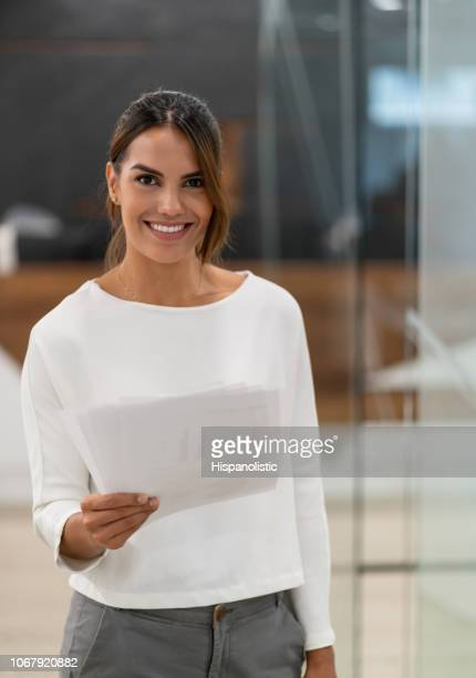 Gorgeous businesswoman at the office looking at camera smiling while holding documents