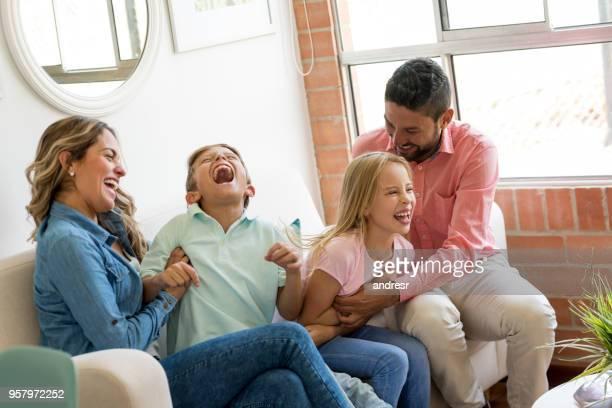 herrliche paar zu hause spielen mit ihren kindern kitzeln sie während sie lachen - kitzeln stock-fotos und bilder