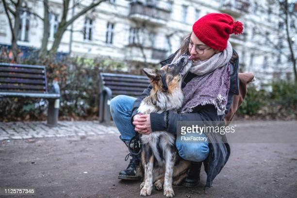 magnífico perro lamiendo una chica hipster en la calle - collie fotografías e imágenes de stock