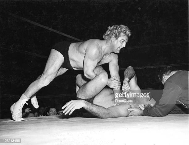 Gorgeous George gets a leg hold on Ralph Garibaldi during their wrestling bout at the Amphitheater in Chicago IL 1949 George owns 88 different...