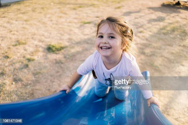 gorgeous girl playing on a playground's slide - sliding stock pictures, royalty-free photos & images