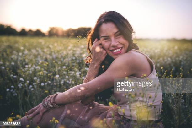 gorgeous girl sitting in the flower field - innocence stock pictures, royalty-free photos & images