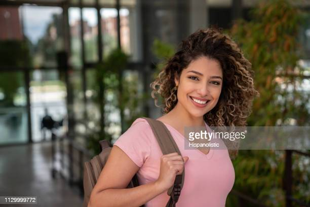 gorgeous latin american female student holding her backpack while facing camera smiling - hispanolistic stock photos and pictures