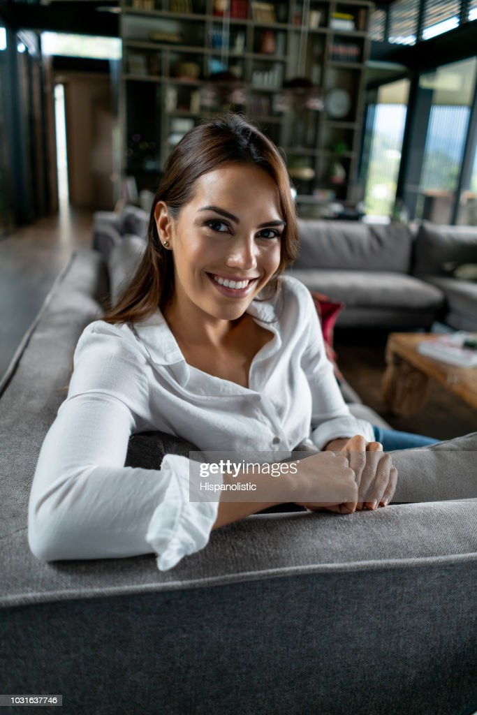 Gorgeous latin american woman at her apartment relaxing on couch and looking at camera smiling : Stock Photo
