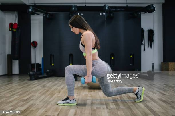 gorgeous long-haired girl working out at her local health club - culi foto e immagini stock