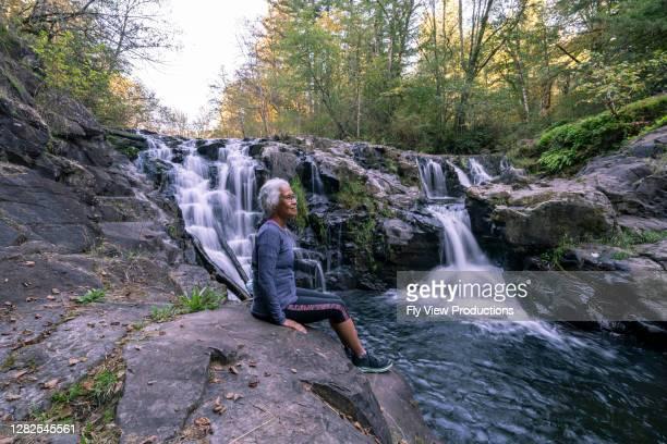 gorgeous mature woman enjoying nature - hawaiian waterfalls stock pictures, royalty-free photos & images