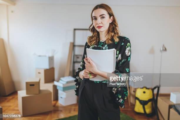 gorgeous real estate agent in a boxed apartment - house rental stock photos and pictures