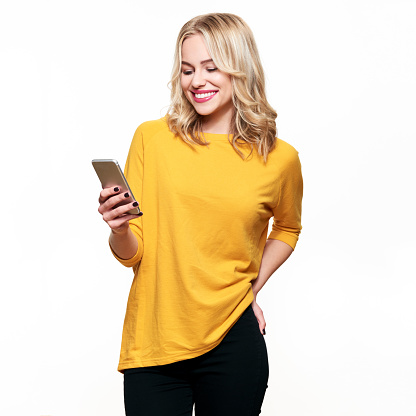 Gorgeous smiling woman looking at her mobile phone. Woman texting on her phone, isolated over white background. 1057104560