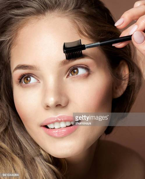 gorgeous woman applying make up - eyebrow stock pictures, royalty-free photos & images
