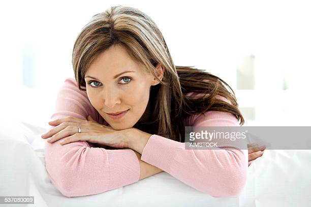 gorgeous woman relaxing on bed - 40 44 jaar stockfoto's en -beelden
