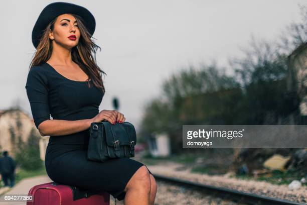 Gorgeous woman sitting on the suitcase and waiting for the train on railroad station