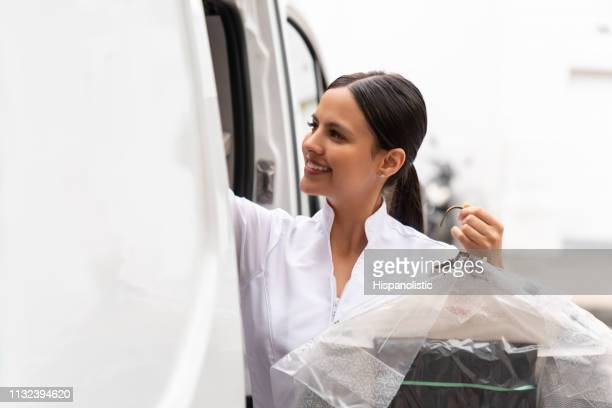 gorgeous woman taking dry cleaned clothes in delivery van ready to give them to customers - dry cleaned stock pictures, royalty-free photos & images