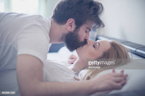 gorgeous young couple kissing in the bed in the morning - bacio sulla bocca foto e immagini stock