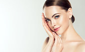 Gorgeous, young woman with clean, fresh skin is touching own face. Facial treatment.
