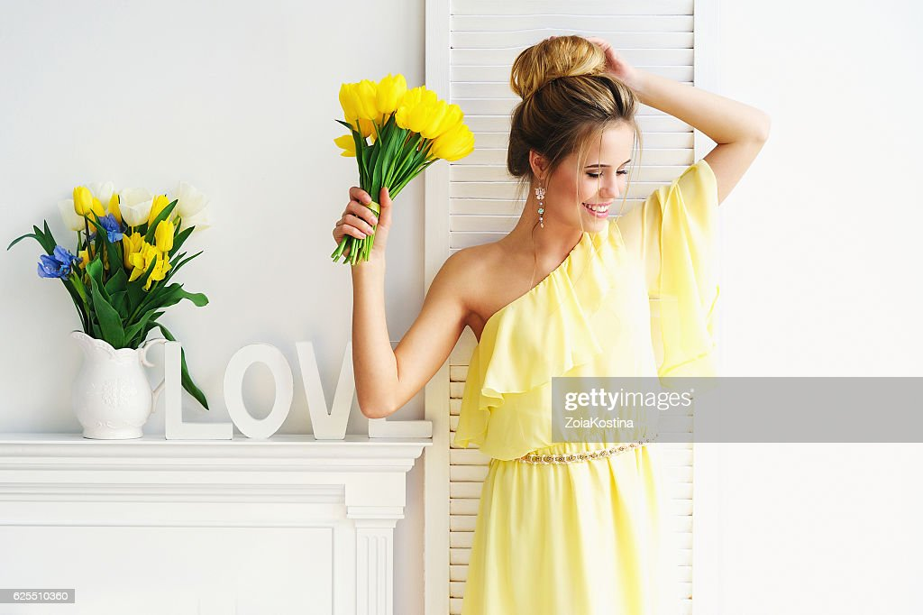 Gorgeous young woman with yellow tulips : Stock Photo