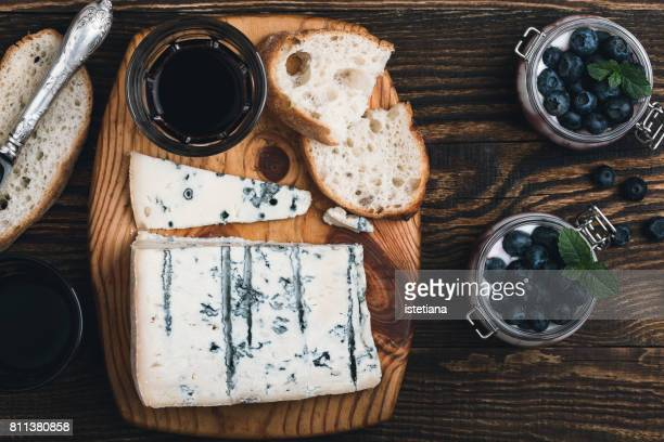 Gorgonzola cheese on wooden cutting board and dessert panna cotta