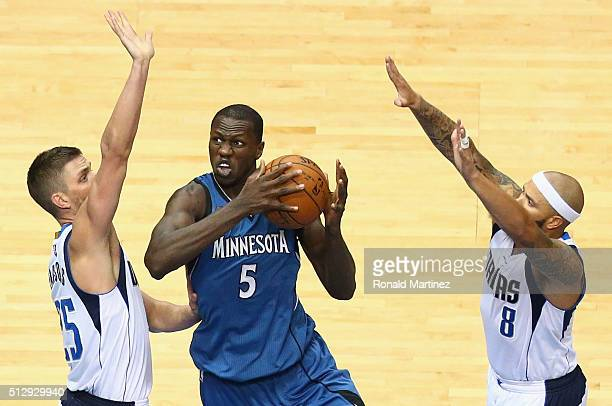 Gorgui Dieng of the Minnesota Timberwolves dribbles the ball against Chandler Parsons and Deron Williams of the Dallas Mavericks at American Airlines...