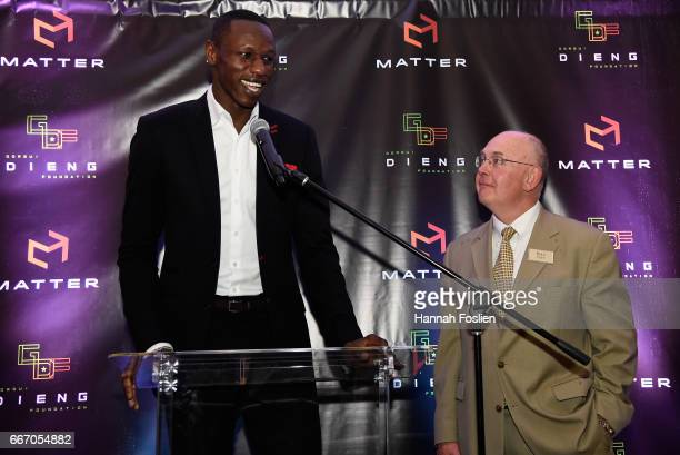 Gorgui Dieng of the Minnesota Timberwolves speaks to those in attendance while Bill Popp Minority Owner of the Minnesota Timberwolves looks on during...