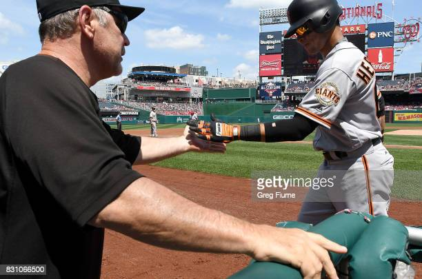 Gorkys Hernandez of the San Francisco Giants celebrates with manager Bruce Bochy after scoring in the second inning against the Washington Nationals...