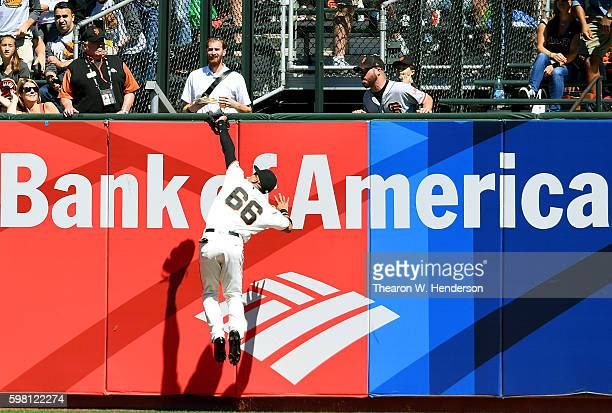 Gorkys Hernandez of the San Francisco Giants leaps into the wall to make the catch while taking a hit away from Paul Goldschmidt of the Arizona...