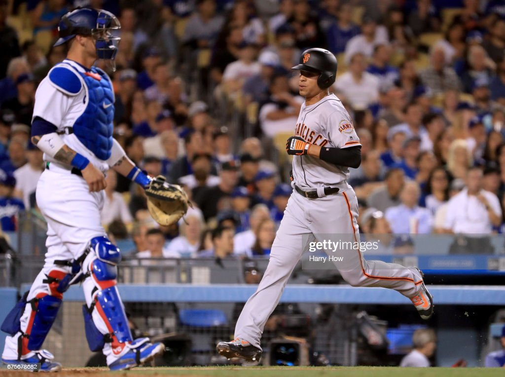 Gorkys Hernandez #66 of the San Francisco Giants scores a run in front of Yasmani Grandal #9 of the Los Angeles Dodgers to take a 4-2 lead during the fifth inning at Dodger Stadium on May 1, 2017 in Los Angeles, California.