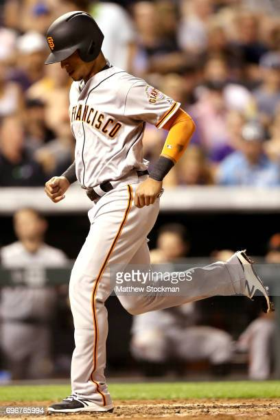 Gorkys Hernandez of the San Francisco Giants scores on a Austin Slater single in the ninth inning against the Colorado Rockies at Coors Field on June...