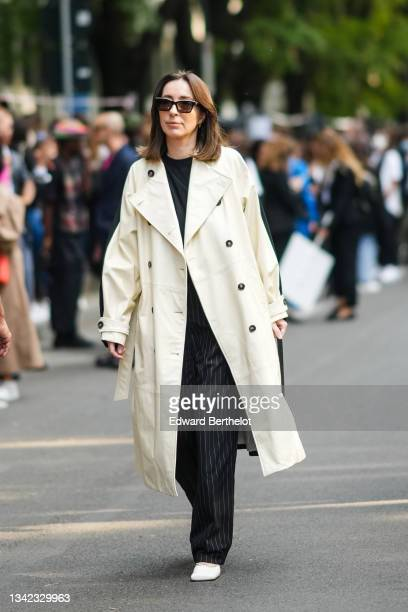 Gosia Boy wears black sunglasses, gold earrings, a black t-shirt, a pale yellow long oversized coat, black with small gray striped large baggy pants,...