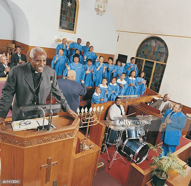 gospel choir and band playing at a church service with a priest standing on a pulpit - gospel stock photos and pictures