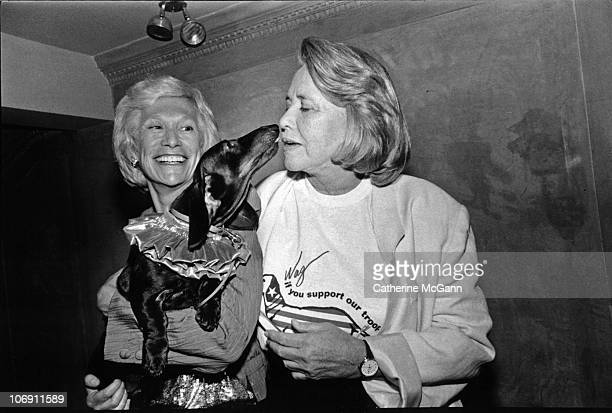 Gossip columnist Liz Smith gets kissed by a dachshund dog held by Iris Love at an event on February 11 1991 in New York City New York