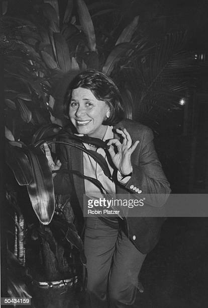 Gossip columnist Liz Smith hiding in a large plant while gathering info on the celebs