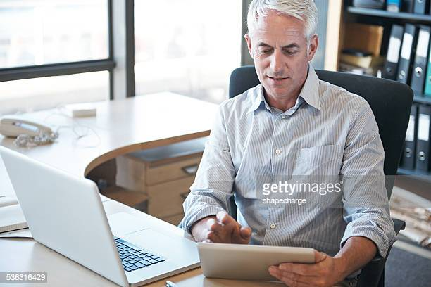 got the latest tech at his fingertips - handsome 50 year old men stock photos and pictures