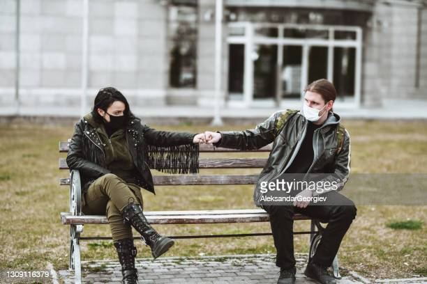 goth couple greeting each other with fist bum while wearing face masks and sitting on bench - punk music stock pictures, royalty-free photos & images