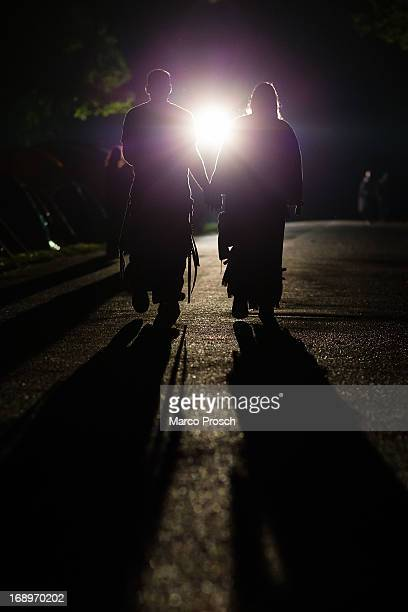 A goth couple walks towards a light at the camping site at the Agra festival area on the first day of the annual WaveGotik Treffen or Wave and Goth...
