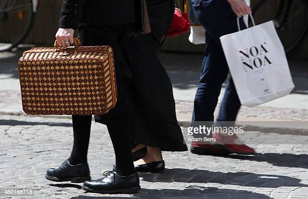 Goth enthusiast walks through town as a local shopper passes during the annual WaveGotikTreffen music festival on June 6 2014 in Leipzig Germany The...