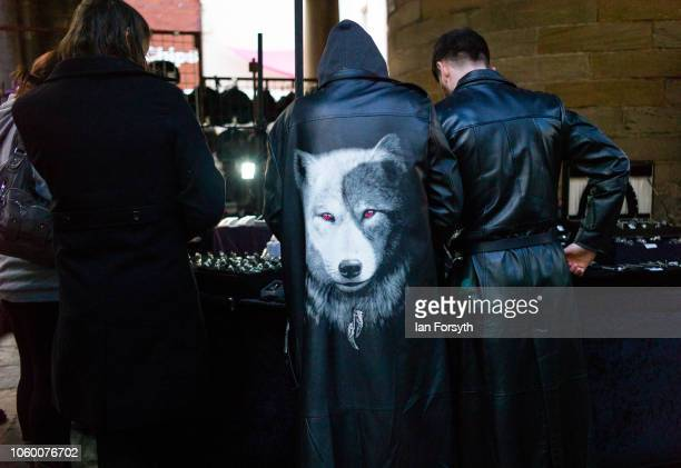 Goth with a decorative wolf design on his jacket browses a stall in a market during Whitby Goth Weekend on October 27 2018 in Whitby England The...