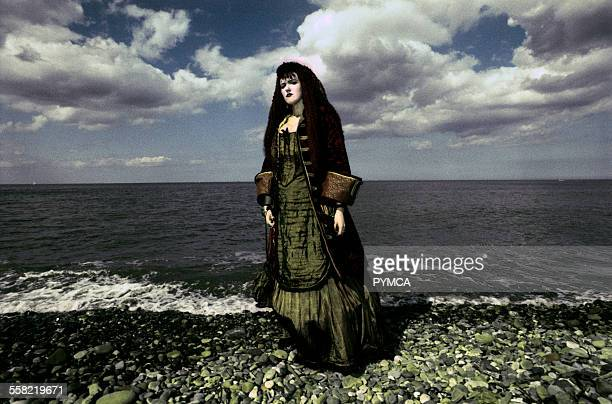 Goth woman standing on a sea shore.