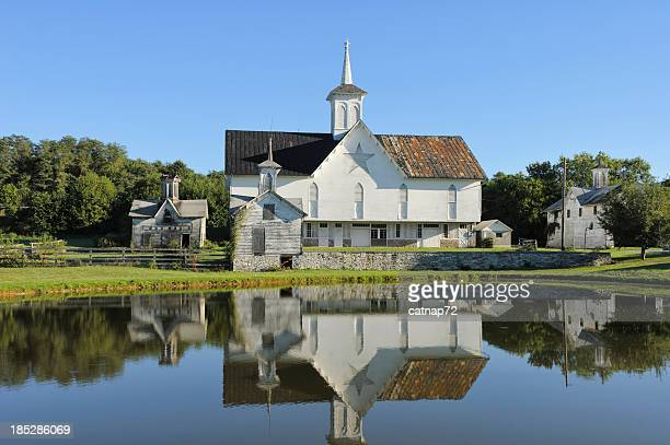 gothic barn reflecting in pond on sunny day - harrisburg pennsylvania stock pictures, royalty-free photos & images