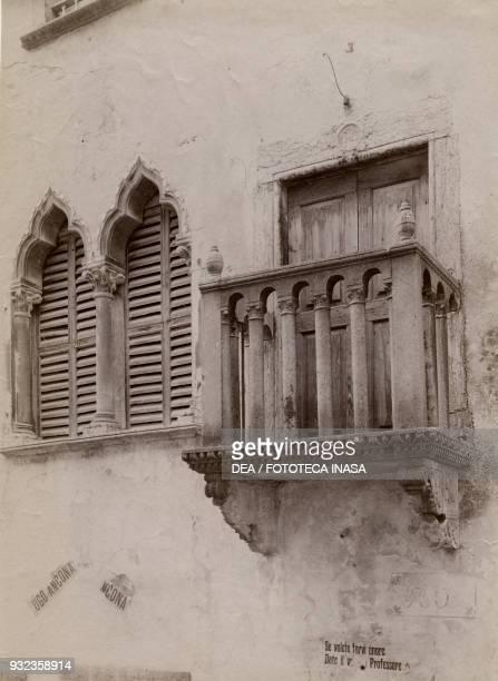 Gothic mullioned window and balcony with campaign posters for Ugo Ancona , Italian teacher and politician, Venzone, Friuli-Venezia Giulia, Italy,...