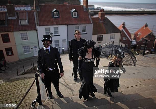 Goths and Steampunks walk through Whitby during Whitby Goth Weekend on April 27 2012 in Whitby England Whitby Gothic Weekend which started in 1994 to...