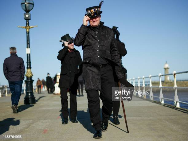 Goths hold onto their hats as they walk along the pier in strong winds as they attend Whitby Goth Weekend on October 27, 2019 in Whitby, England. The...