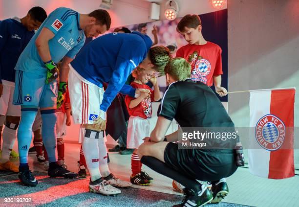Gotoku Sakai of Hamburg and referee Christian Dingert console an escort kidn prior to the Bundesliga match between FC Bayern Muenchen and Hamburger...