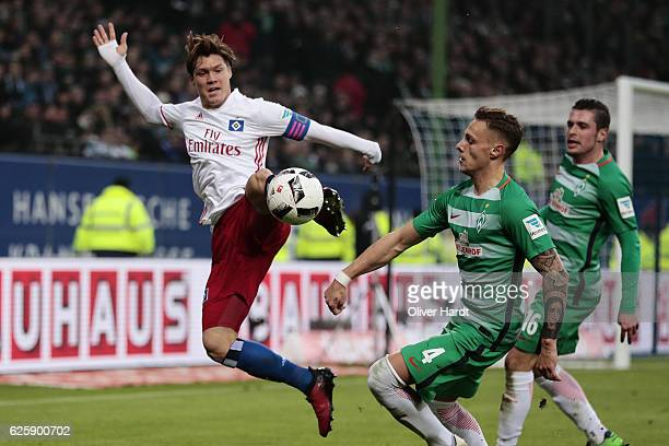 Gotoku Sakai of Hamburg and Robert Bauer of Bremen compete for the ball during the Bundesliga match between Hamburger SV and Werder Bremen at...